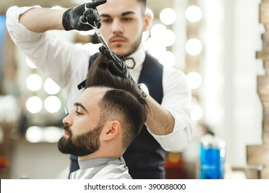 Attractive barber with dark hair wearing white shirt, watch and black gloves doing a haircut for client with scissors at barber shop, lights and mirror at background.