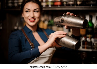 Attractive bartender girl in the white apron holding in her hands two steel cocktail shakers at the bar counter