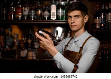 Attractive bartender holding in hands a steel shaker on the bar counter in the dark blurred background