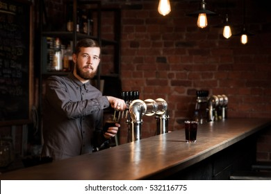 Attractive bartender is pouring a beer