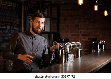 Attractive bartender is pouring a cocktail