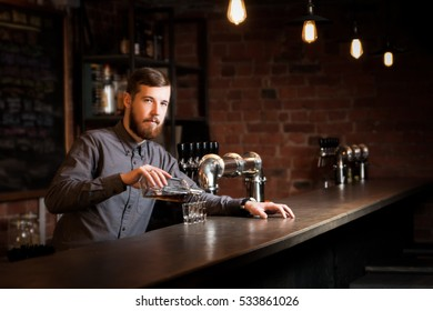 Attractive bartender is pouring a shots