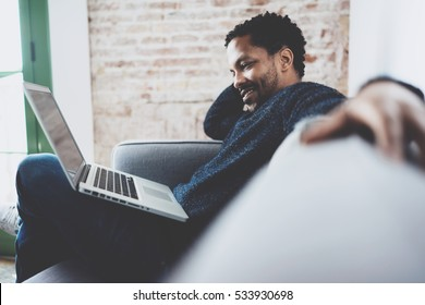 Attractive bearded African man using laptop while relaxing sofa at his modern home studio.Concept of young people enjoying mobile devices.Brick wall on blurred background.Side view