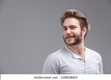 Attractive bearded blond man turning to look over his shoulder and then glancing back at the camera with a smile over grey with copy space