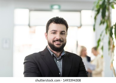 Attractive bearded businessman in office looking at camera smiling looking at camera
