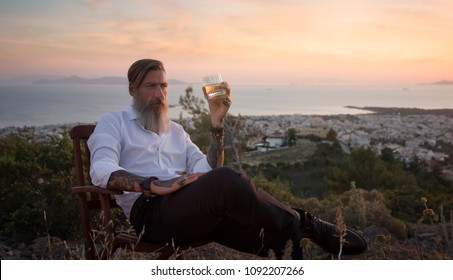 Attractive bearded businessman is sitting on the chair on the mountain and drinking whiskey at sunset