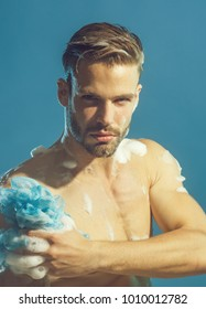Attractive bearded guy washing in bathroom. Man with bristle and concentrated face take shower. Young naked man taking shower with sponge and foam.