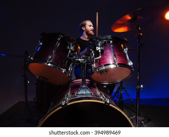 Attractive bearded man drummer sitting and playing on his kit over dark background