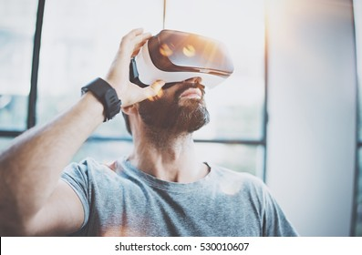 Attractive bearded man enjoyingvirtual reality glasses in modern interior design coworking studio.Home play concept.Smartphone use with VR goggles headset.Flare and sunny effect,blurred background
