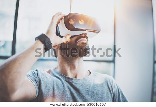 Привлекательный бородатый человек наслаждатьвиртуальной реальности очки в современном дизайне интерьера coworking studio.Home играть concept.Использование смартфона с VR очки гарнитуры.Вспышка и солнечный эффект, размытый фон