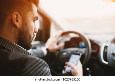 Attractive bearded man texting while driving an expencive car in a sunny weather.