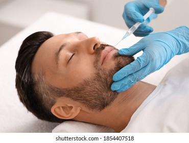 Attractive bearded man visiting aesthetic clinic, getting lips filler, closeup. Middle aged businessman having beauty injection at male spa salon. Face care, anti-aging treatment for men concept