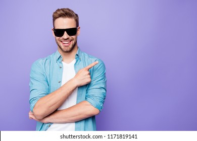 Attractive bearded trendy stylish confident positive cheerful man, wearing denim and sun glasses, pointing with finger aside, over pastel violet purple background, empty blank copy space