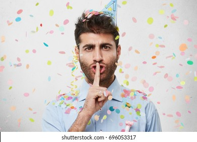 Attractive bearded young Caucasian male in blue shirt holding index finger at his lips, pronouncing Shh as he doesn't want to ruin surprise party on his girlfriend's birthday. Celebration concept