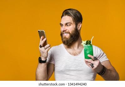 attractive bearded young man talking on the phone with a cocktail