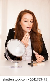 attractive beautidful woman applying lip gloss