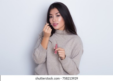 Attractive and beautiful Asian girl paint lips a pink lipstick and looking at the camera. Portrait of smiling make-up girl isolated on white background.