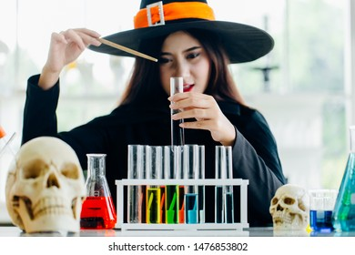 Attractive beautiful Asian woman dressed as a witch using magic wand casting spell to potion in test tube at modern laboratory, Halloween holidays.