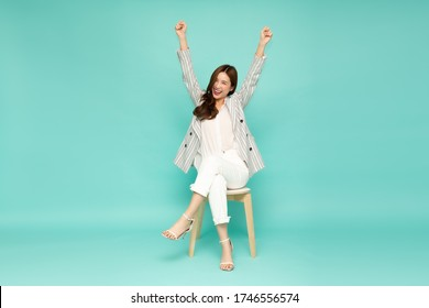 Attractive beautiful Asian woman sitting on white modern chair and hands up raised arms from happiness, Excited businesswoman winner success concept