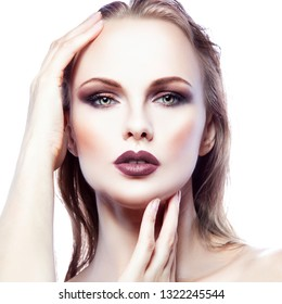 Attractive beautiful fashion model woman beauty face. Bright smokey eyes make-up, clean skin, hair style, modern dark lipstick. White background. Isolated