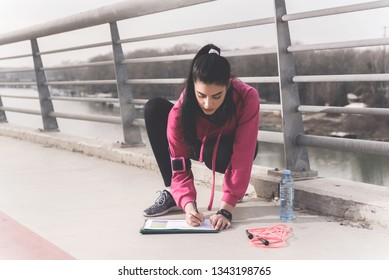 Attractive beautiful female personal trainer writing down fitness parameters, Healthy and active lifestyle concept