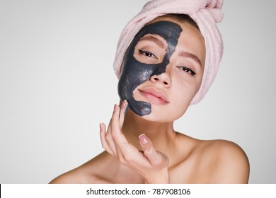 an attractive beautiful girl with a pink towel on her head applied a clay mask