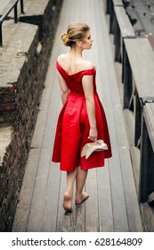 Attractive beautiful girl in a red dress holding her shoes in their hands and bare feet walking on wooden bridge