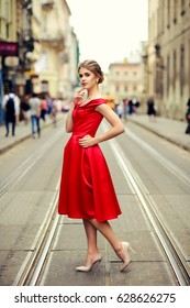 Attractive beautiful girl in a red dress standing on tram tracks on the background of the city