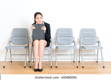 attractive beautiful suit female student holding meeting file sitting on wood floor chair and looking at empty area thinking work planning feeling frustrated in white wall room.