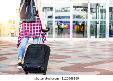 Attractive beautiful traveler woman is waking to airport and dragging suitcases, carrying backpack in front of gateway. Charming tourist girl get long weekend holiday. She will travel foreign country