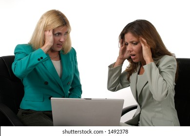 Attractive and beautiful two business woman team working at a laptop computer together.  Shot on white.