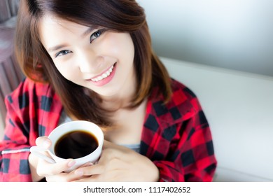 Attractive beautiful woman is feeling fresh in the holiday morning when charming beautiful women drinks back coffee in living room at house with smiley face. Beautiful asian girl feel happy, relaxing