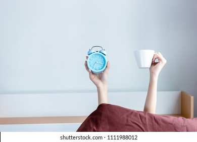 Attractive beautiful woman is holding alarm clock and a coffee cup and raise it to the air for showing that It is a coffee time in morning. Beautiful girl love to drink coffee in morning. copy space