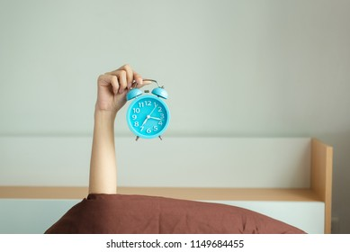 Attractive beautiful woman is holding alarm clock and raise it to the air for showing that It is  time in morning. Beautiful girl lazy on wakeup on the bed ,copy space.