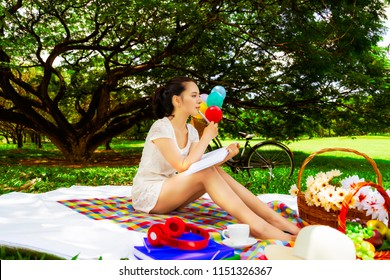 Attractive beautiful woman is thinking and composing poems for writing to a book. Charming beautiful woman love composing novel at beautiful park. Gorgeous girl hold pen and notebook. park background