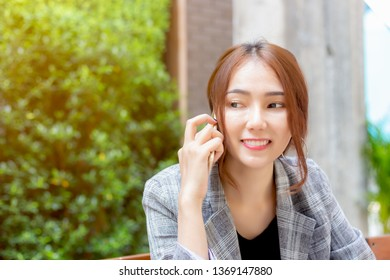 Attractive beautiful young asian business woman talking about business with her boss or client by using smartphone at foreign country. Charming beautiful young woman gets happy when boss get satisfy