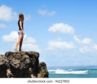 Attractive Beautiful Young girl on the rock looking over the ocean