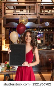Attractive, beautiful young girl in red dress, smiling, holding black board, with balloons in restaurant background