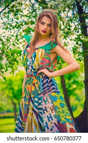 attractive beautiful young model in colorful dress in summer garden