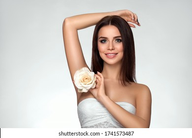 Attractive beautiful young woman with white rose near her face. Spa concept of body skin care. Beauty smiling girl with raised hand up. Armpit and hair removal