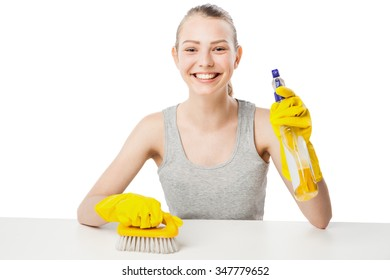 attractive beautiful young woman in yellow rubber gloves sits at table holding brush and spray isolated over white