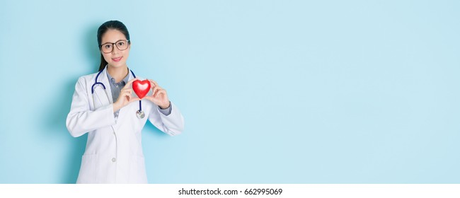 attractive beauty female cardiologist looking at camera smiling in blue background and showing heart healthy care concept with banner crop for copy space.