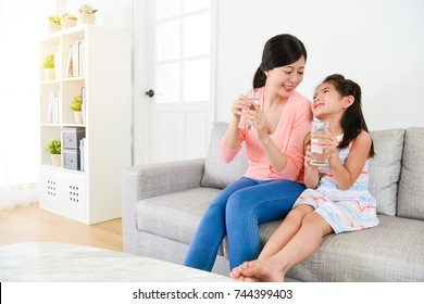 attractive beauty female little kid children with mother sitting on sofa couch relaxing and holding water cup looking each other.