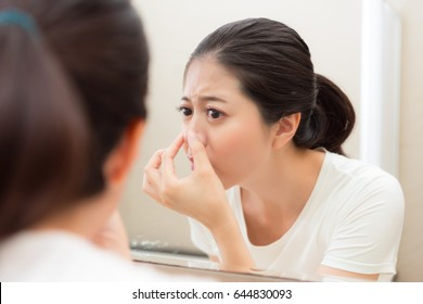 attractive beauty girl holding nose found acne problem, standing in bathroom and looking at reflection in mirror.