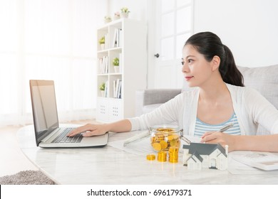 attractive beauty girl using mobile laptop searching personal online account deposit when she planning buying new house for herself.