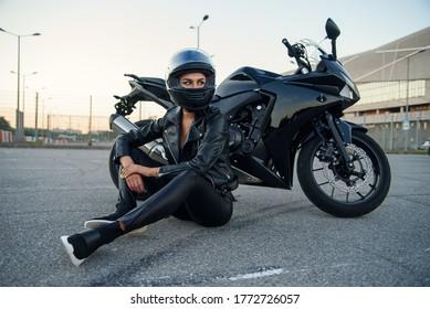 Fahrerin in schwarzem Lederjacke und Vollkopfhelm sitzt in der Nähe von stilvollen Sportmotorrädern auf städtischen Parkplätzen. Reisen und aktives Lifestyle-Konzept.