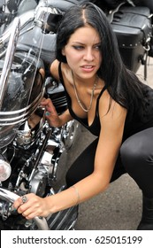 attractive biker woman and her motorcycle at the motorbike show,vertical composition