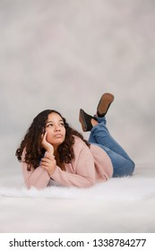 Attractive biracial high school senior laying down on floor posing for portraits with serious expression