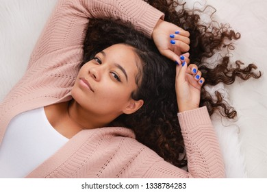 Attractive biracial high school senior laying down on floor posing for portraits