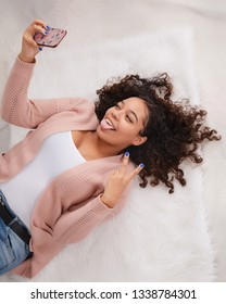 Attractive biracial high school senior laying down on floor smiling and posing for selfie